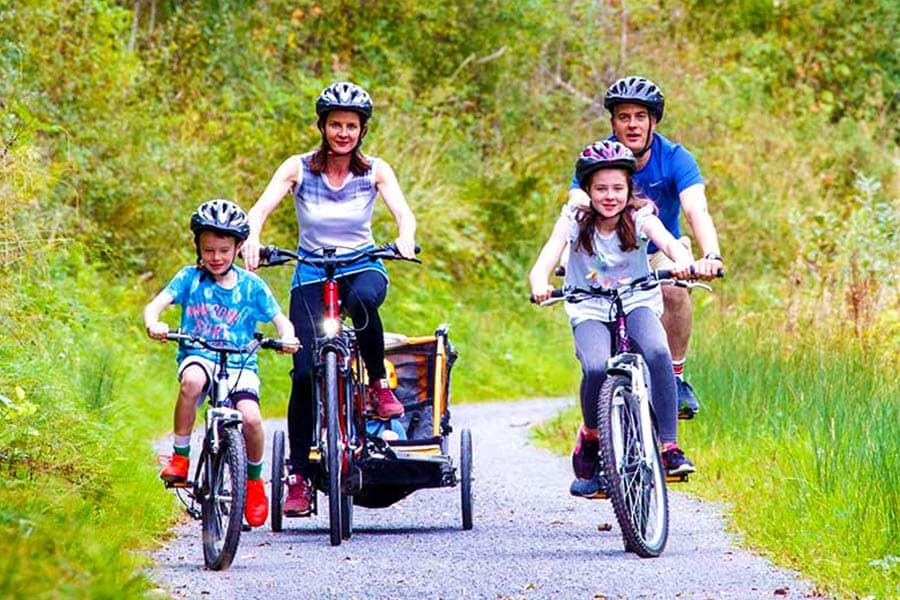 Family cycling on canal side path